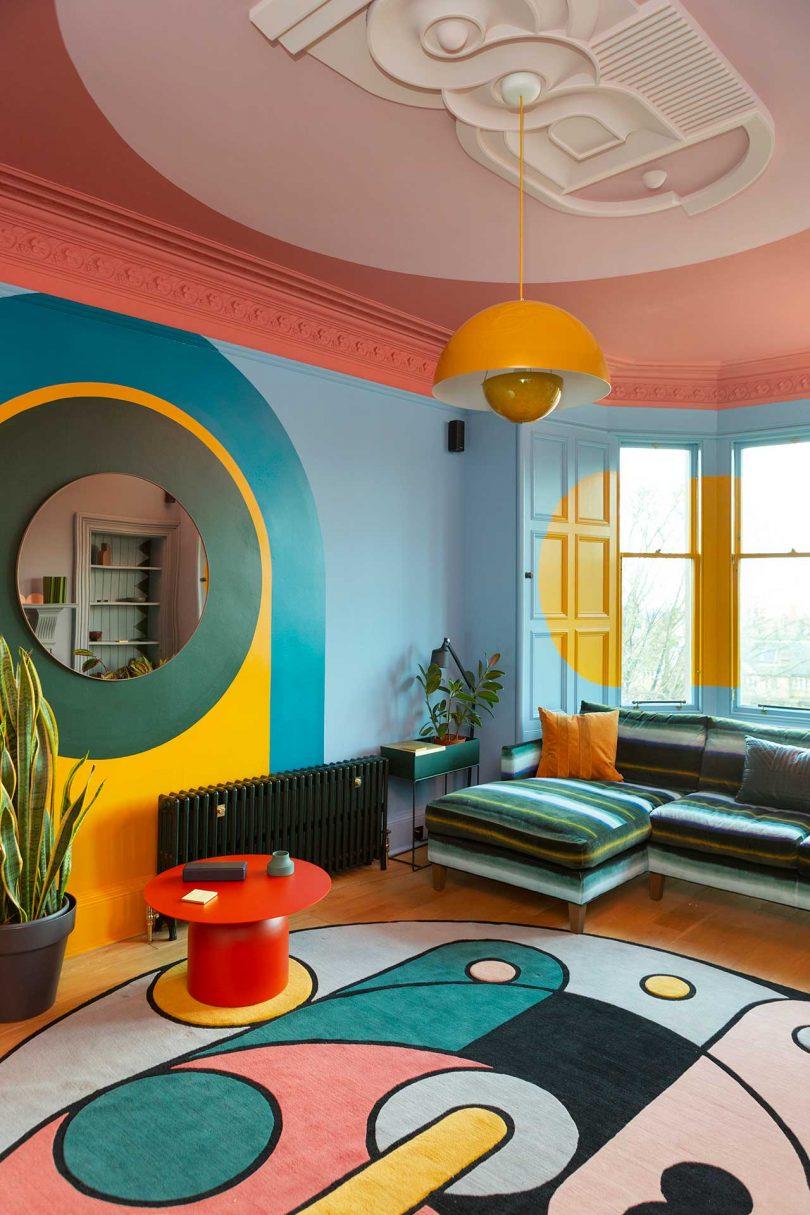 sala de estar colorida com tapete estampado e sofá listrado