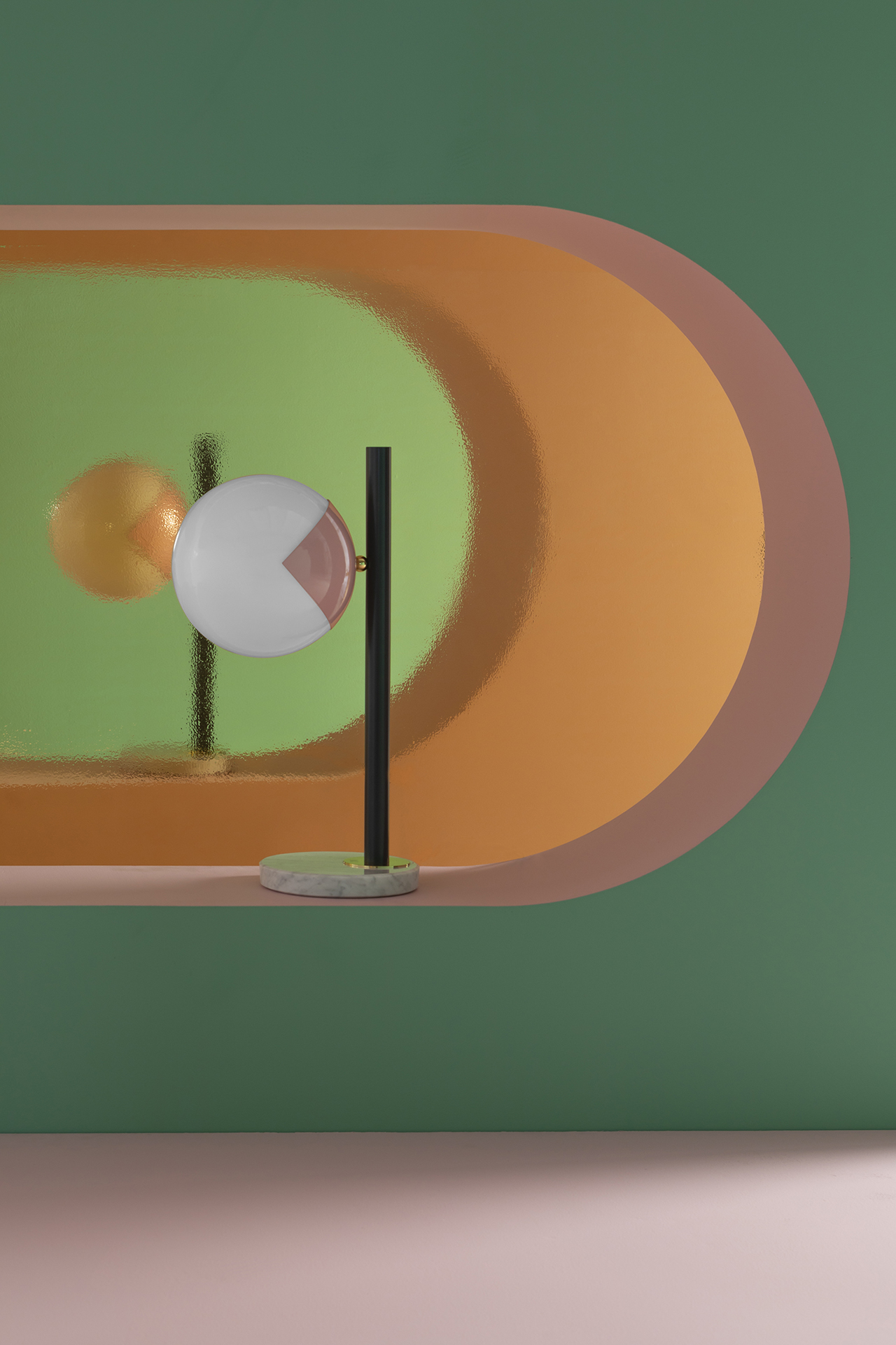black and pink table lamp perched in wall opening in green, pink, and orange space