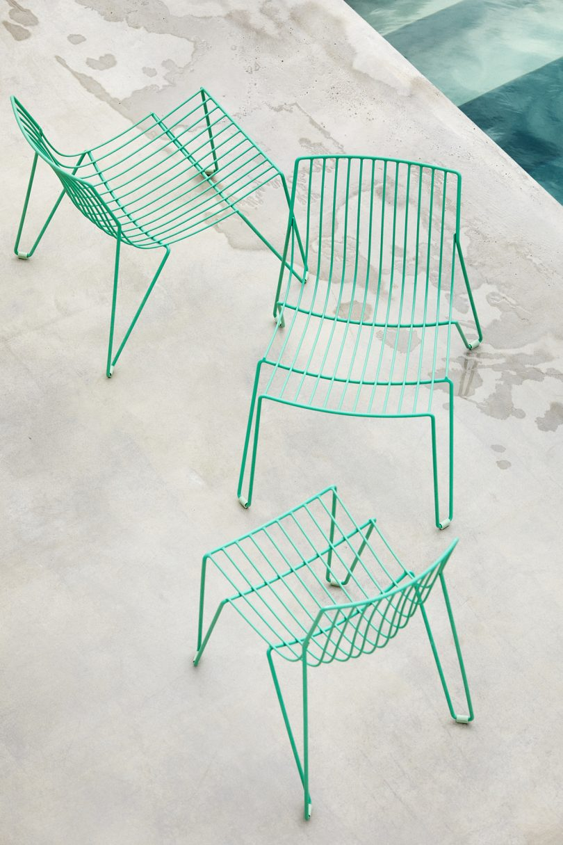 three green wire chairs on cement