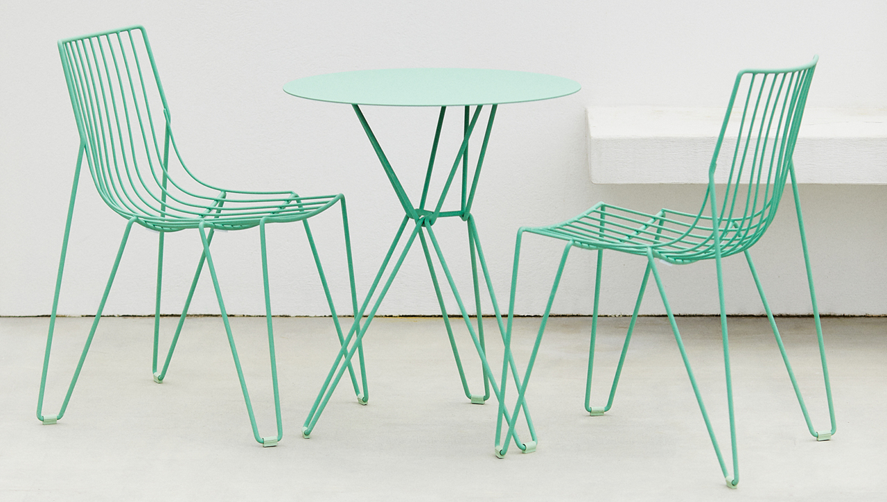 two green chairs and green table sitting on cement