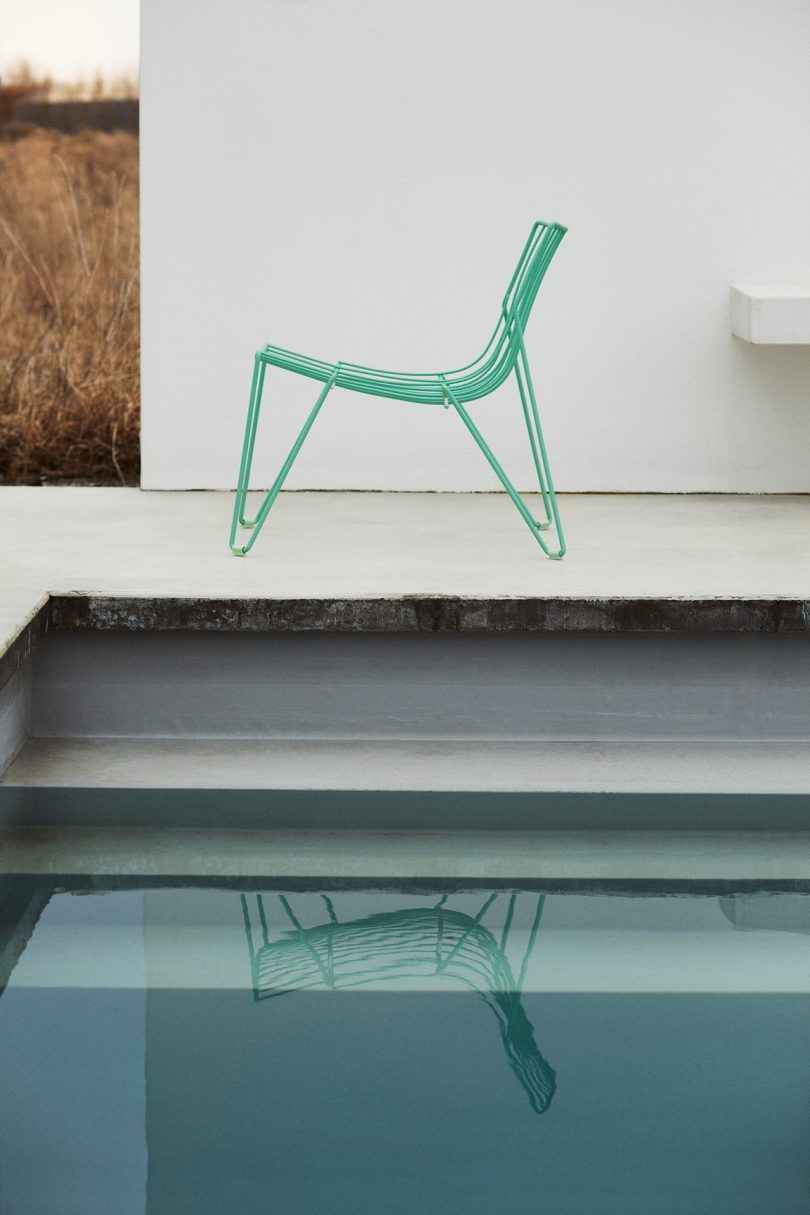 green wire chair sitting poolside next to pool stairs