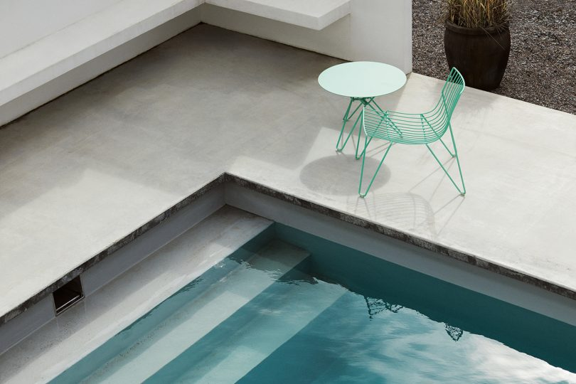 green wire chair and table sitting poolside next to pool stairs
