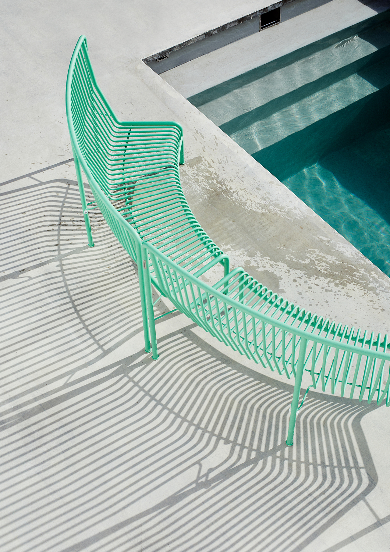 green wire bench poolside
