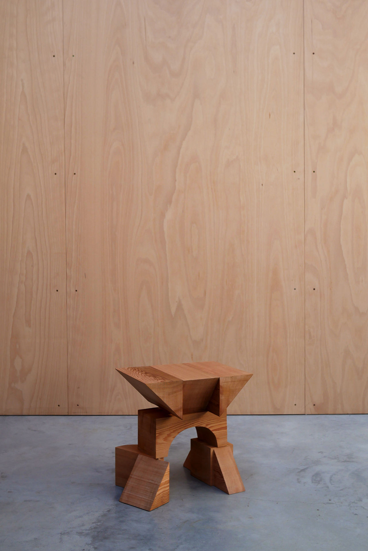 asymmetrical red cedar chair on concrete floor in front of wood wall