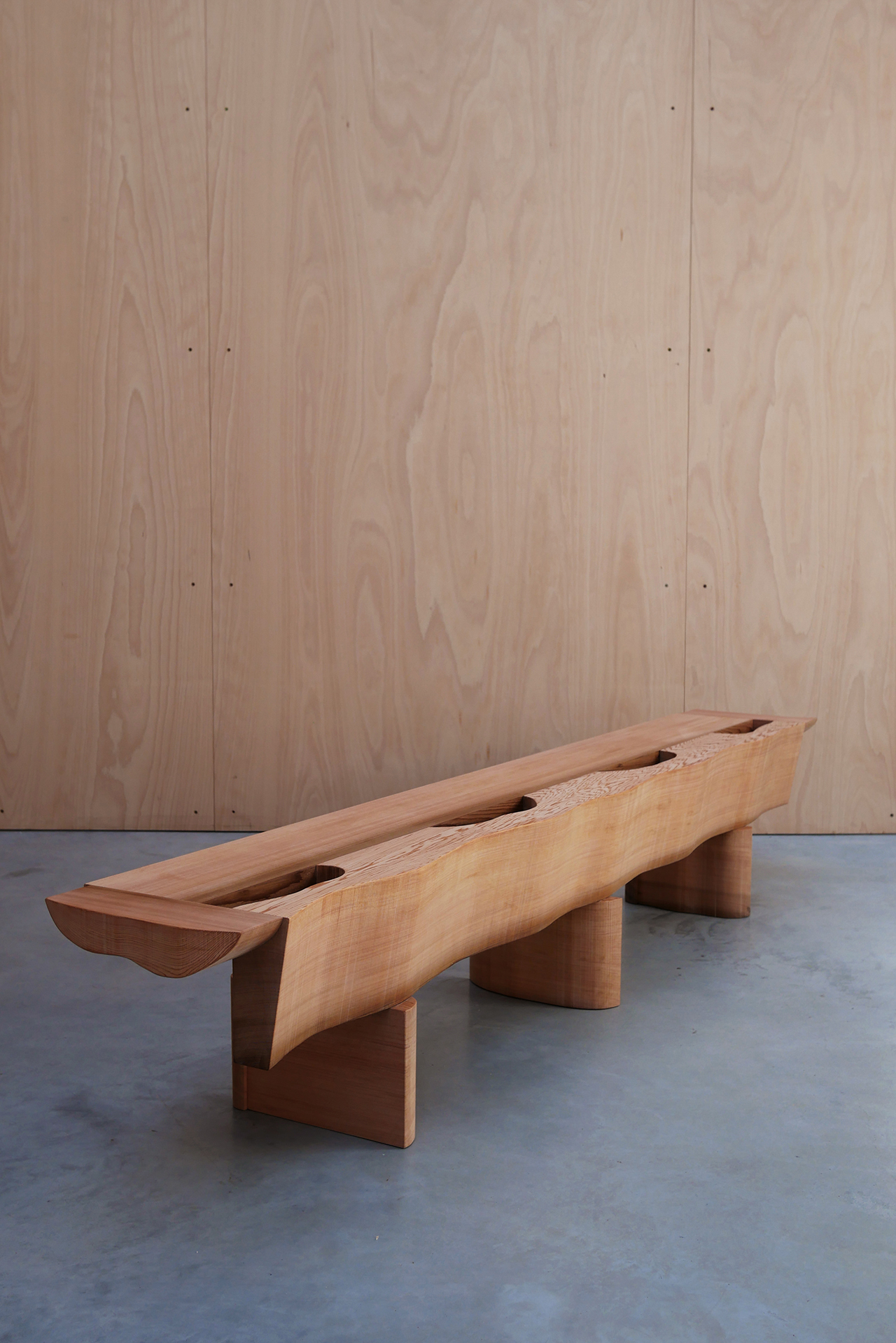 asymmetrical red cedar bench on concrete floor in front of wood wall