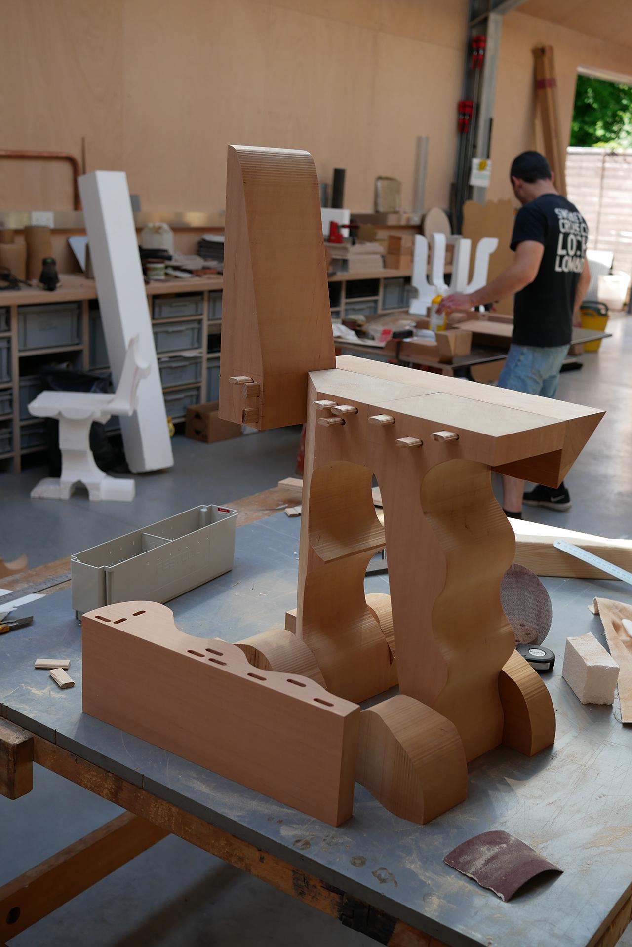 asymmetrical red cedar chair being put together in workshop