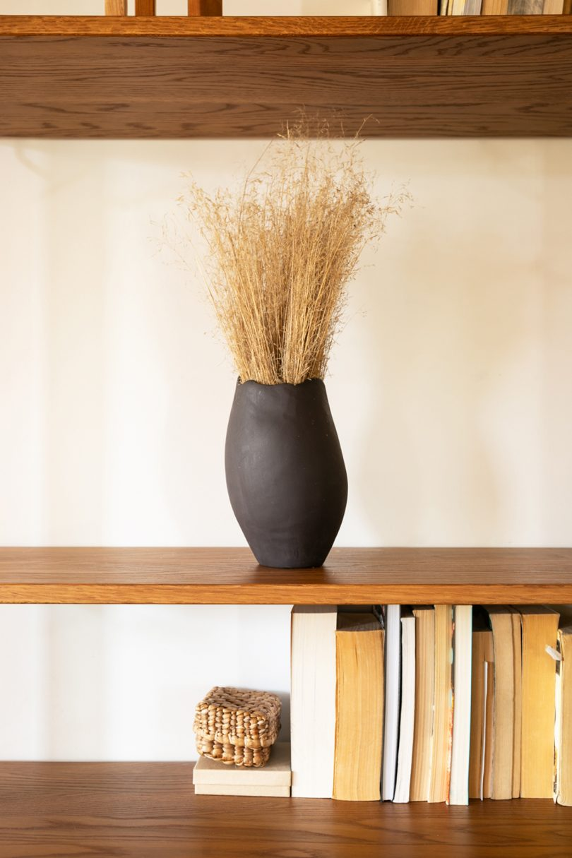 black vase filled with wheat on bookshelf