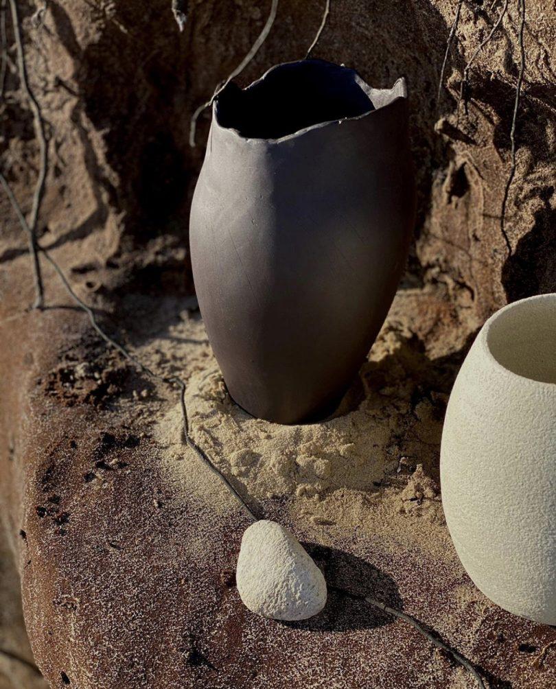 black vase and white vase sitting on rock