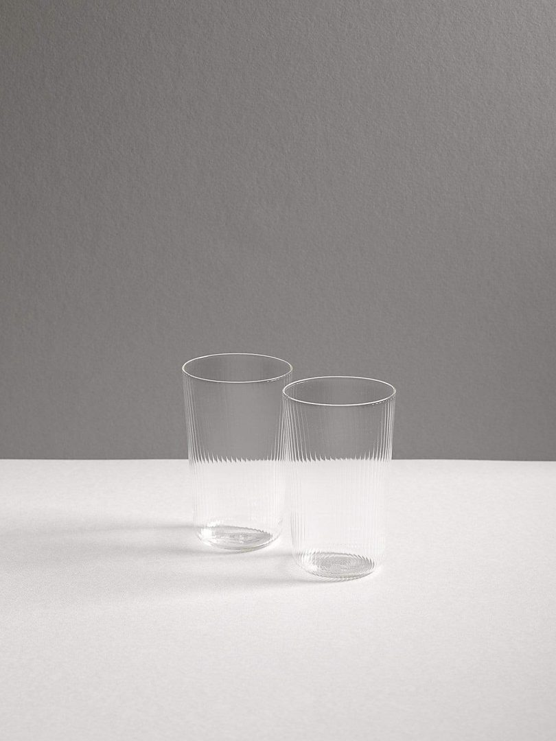 two clear glass tumblers on a white and grey background