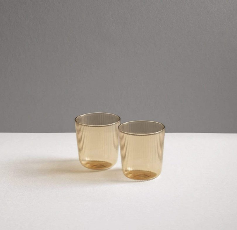 two clear light brown tumblers on a white and grey background
