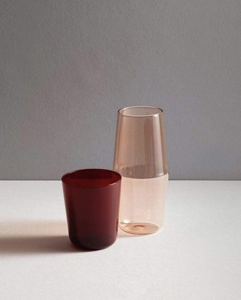 red glass tumbler and pink glass carafe on a white and grey background