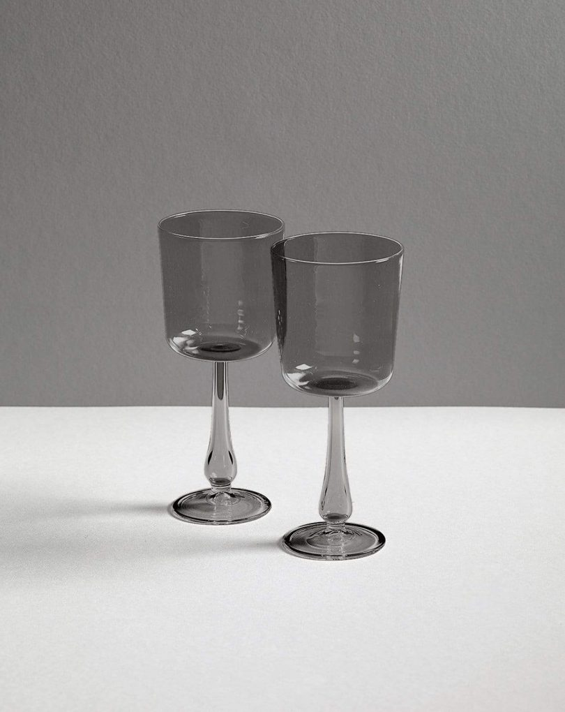two grey wine glasses on a white and grey background
