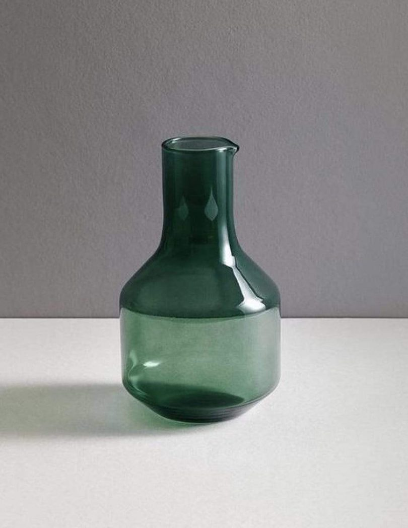 dark green glass carafe on a white and grey background