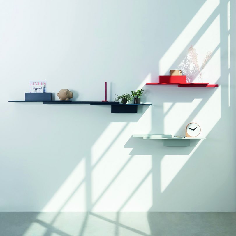 three shelves of varying sizes and colors accessoried and hanging on a white wall with sunlight streaming in