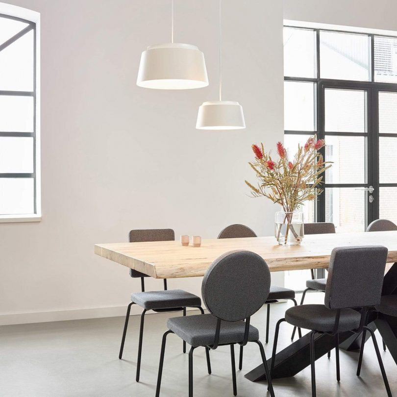 dining space with table, chairs, floral arrangement, and two white pendant lights