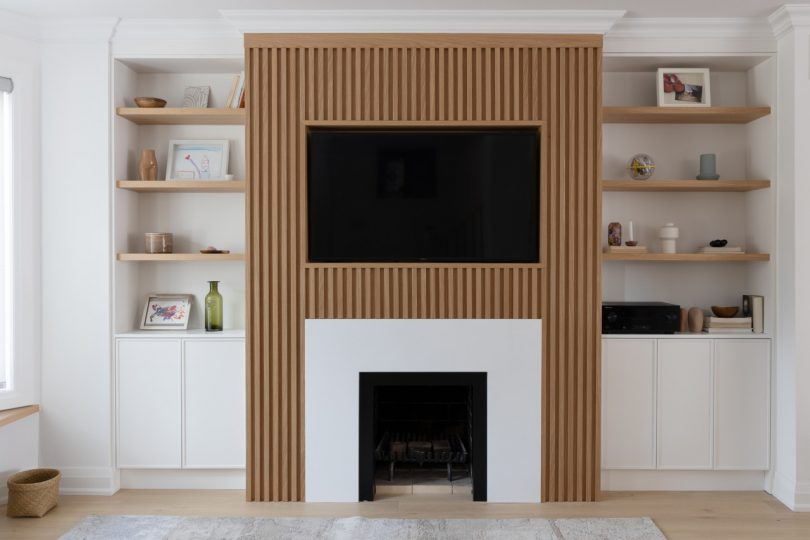 slatted wood wall with fireplace and built-ins