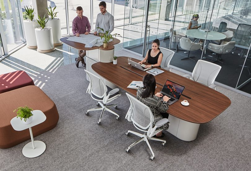 conference table with office chairs and standing workspace