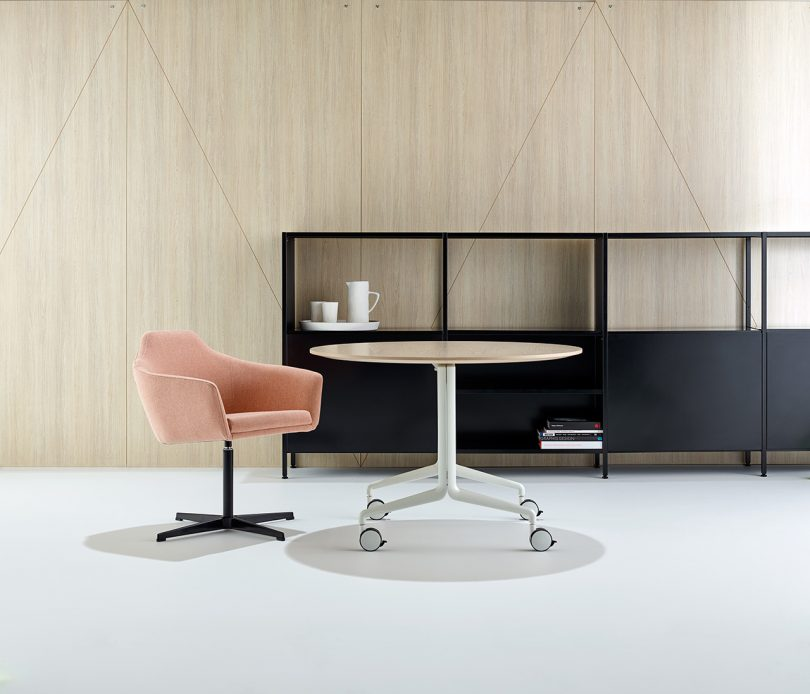 black shelving, pink conference room chair, and round table with wheels