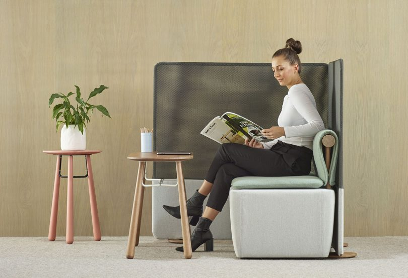 woman sitting in privacy booth with two side tables