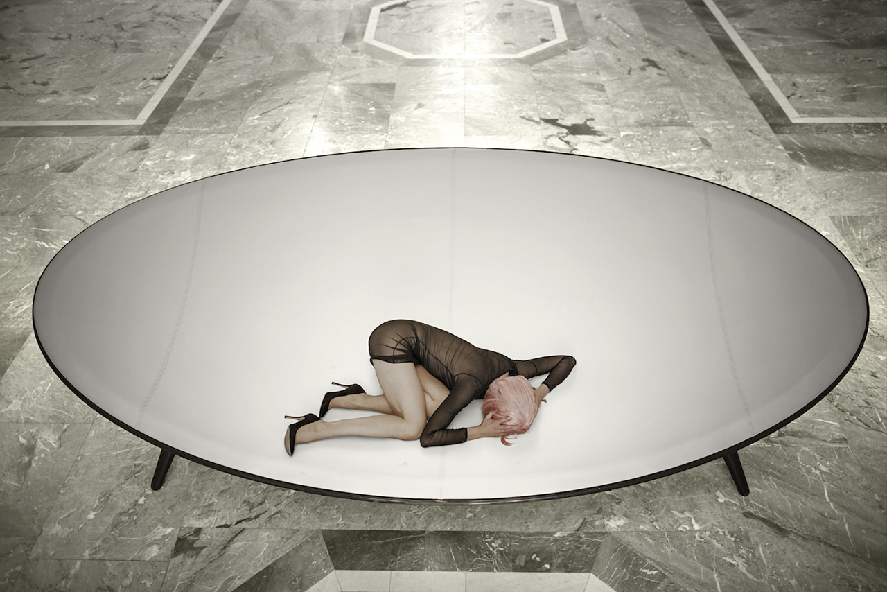 orb-like white and black lounge with woman in marbled interior space