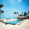 orb-like lounge on the beach between a pool and the ocean with palm trees and blue sky