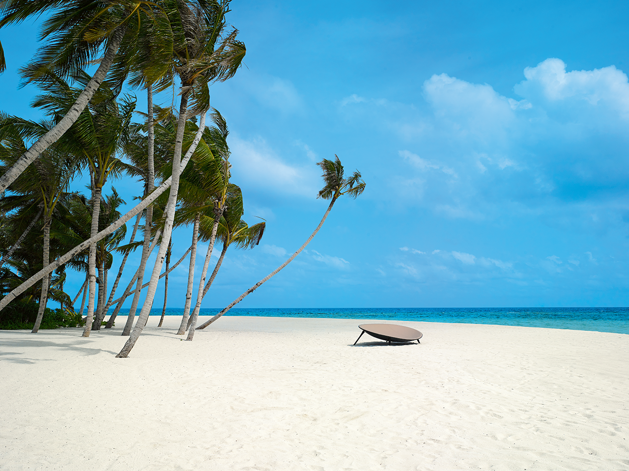 orb-like lounge in the distance on a beach with sand, palm trees, and blue sky