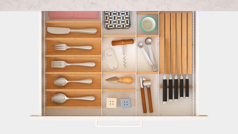 overhead photo of adjustable drawer organizer with kitchen utensils