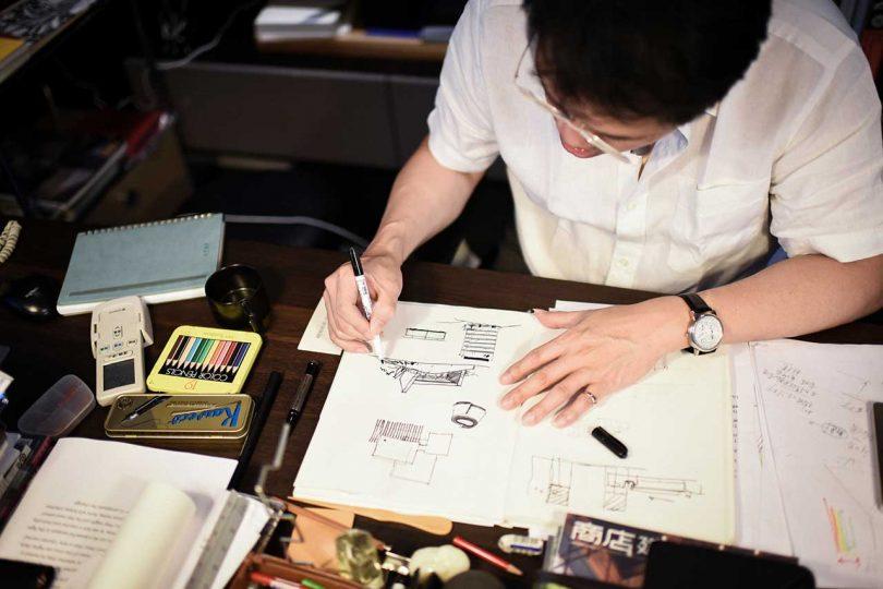 man drawing at desk