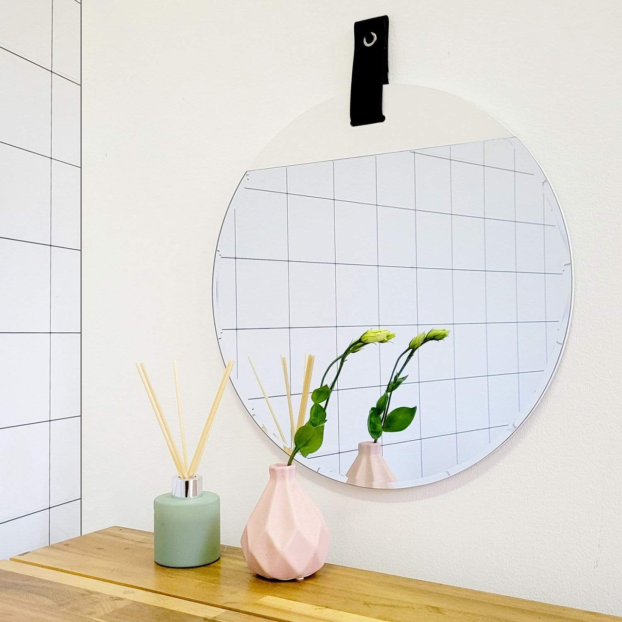 round wall mirror hanging on white wall