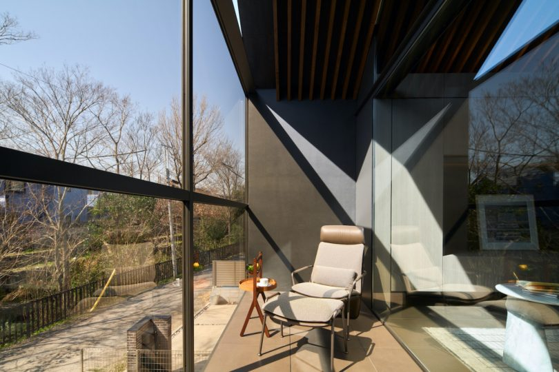 outdoor balcony with chair and ottoman overlooking yard