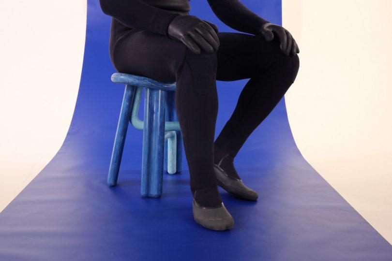 pessoa com roupa de neoprene sentada em um banquinho azul