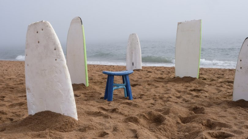 stool on beach with bodyboards