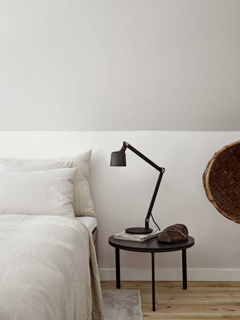 edge of bed with side table and lamp