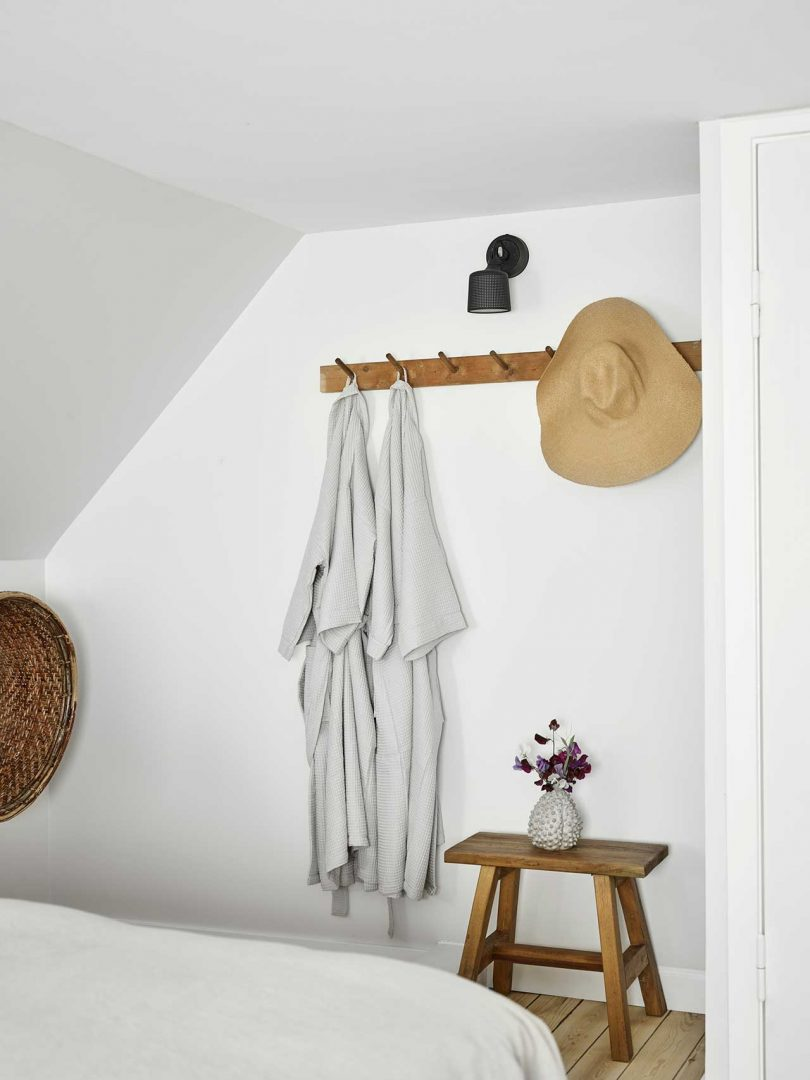 wall rack holding bathrobes and hat
