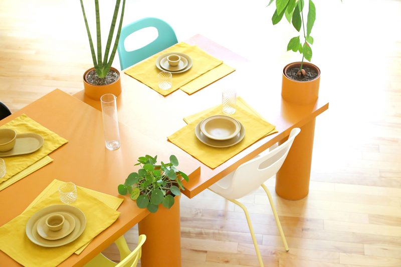 orange sculptural table with plants set for meal