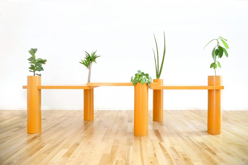 orange sculptural table with plants