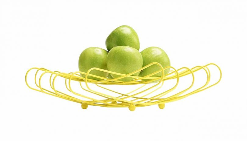 bright yellow wire fruit bowl with green apples