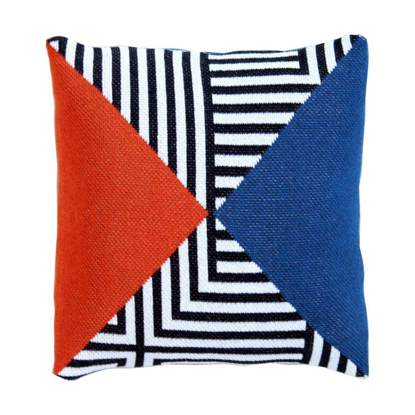 knitted pillow cover with graphic black + white pattern and blocks of red and blue
