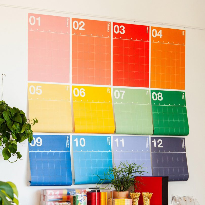 while wall covered in a rainbow of calendar pages
