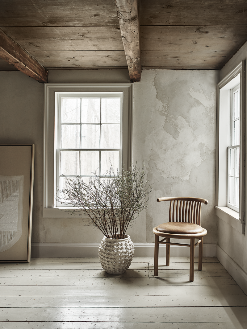 living space with window, large vase, and chair