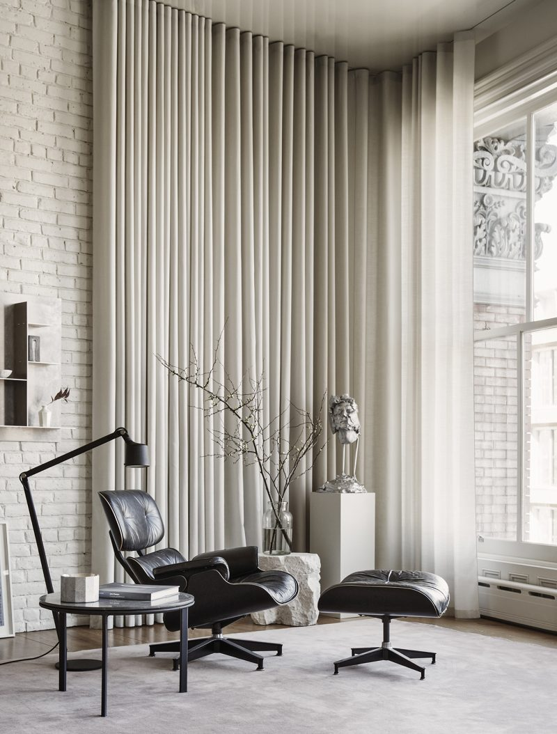 living space with Eames chair and footrest, long curtain, and large window