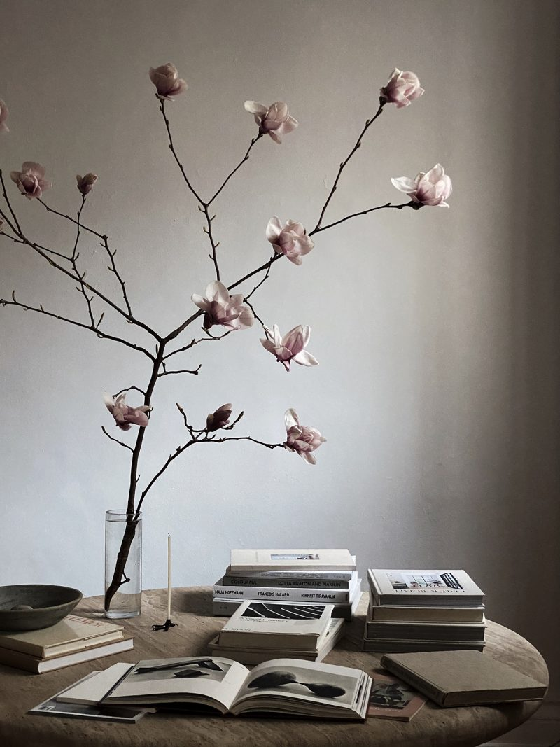 table with large vase, branch, and book stacks