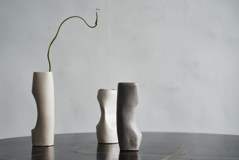 three curvaceous vases sitting on a dark reflective surface