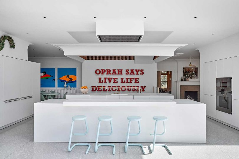 white kitchen with oprah saying on wall in red