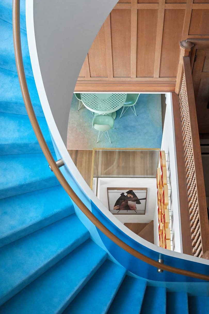 view looking down through floors with blue stairs