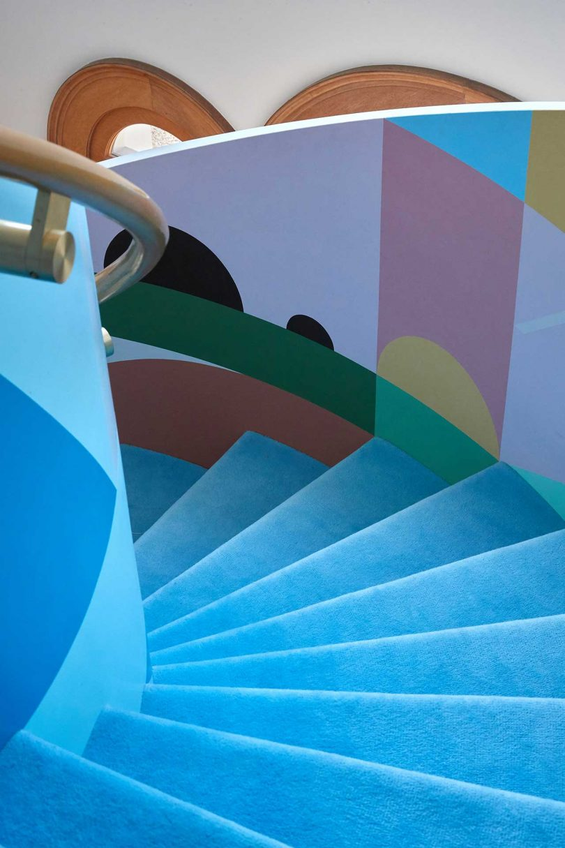 a curved staircase with bright blue and geometric graphics
