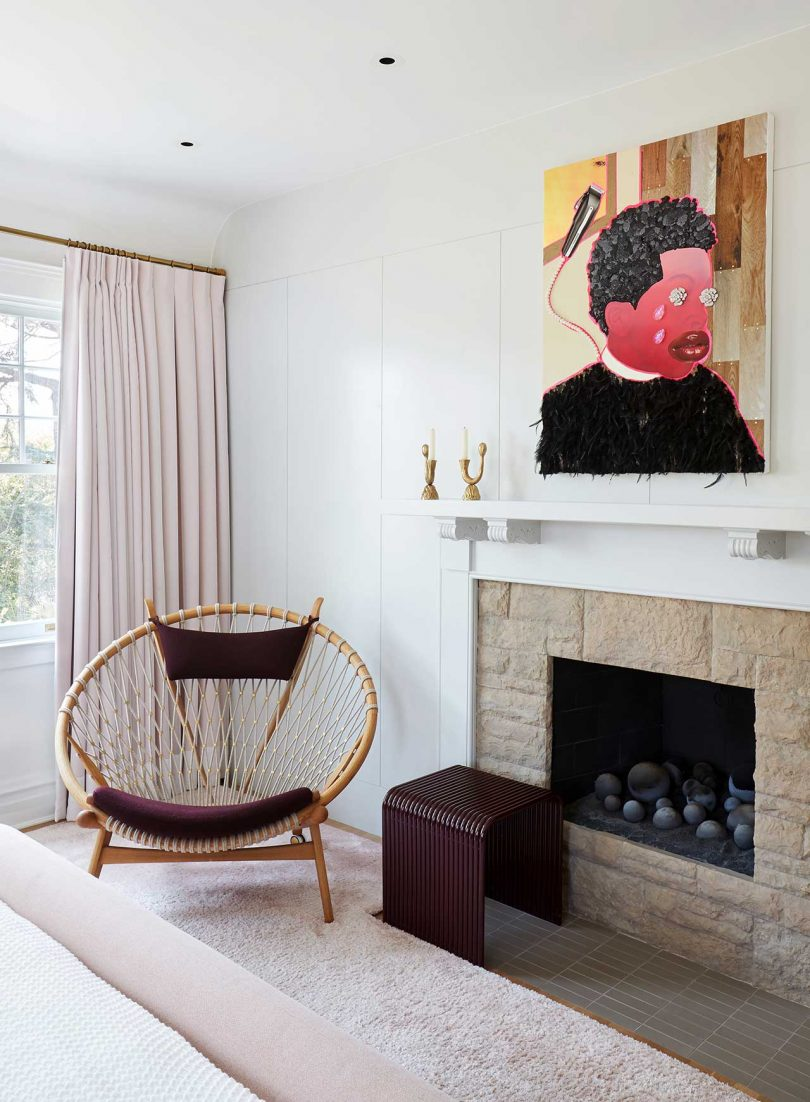 corner of bedroom with fireplace, chair and art