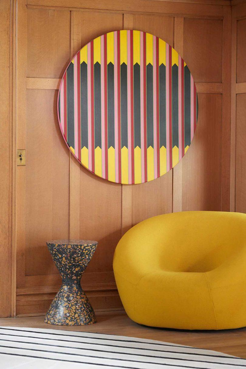 modern yellow chair in corner with circular art on wall