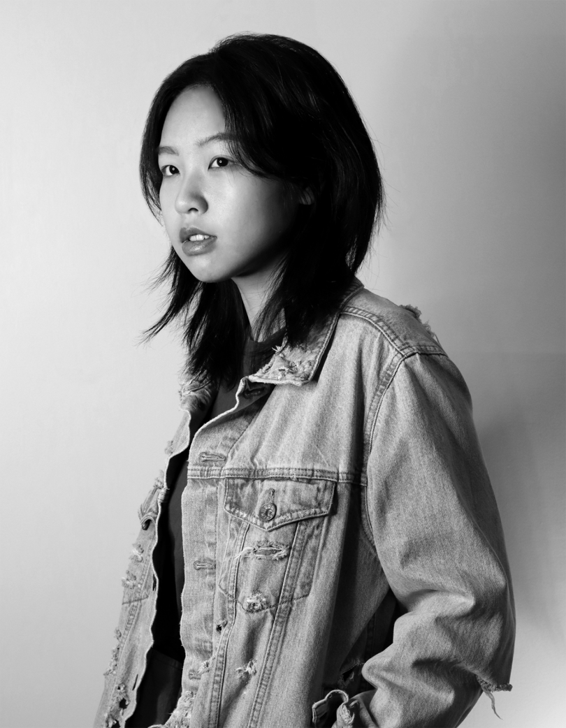 black and white photo of woman with dark medium length hair wearing jean jacket