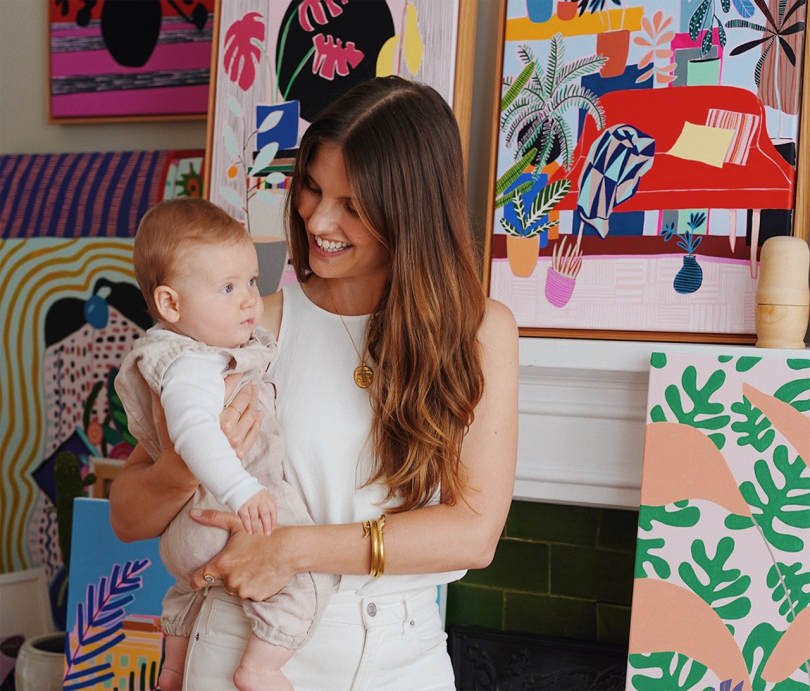 light skinned woman holding child standing in front of artworks